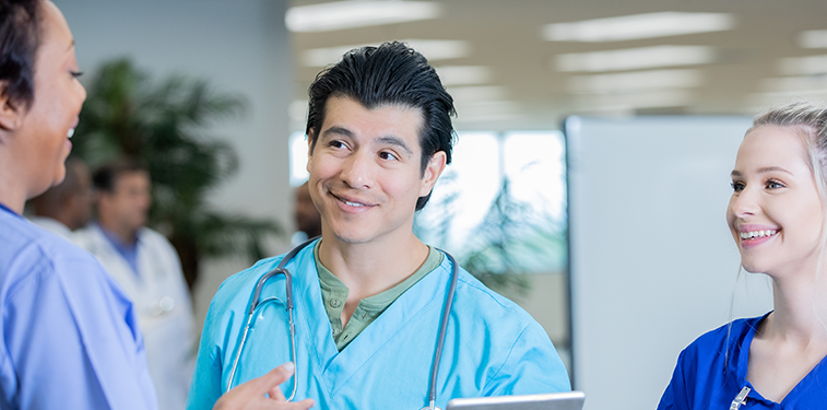 Latino male in professional setting holding tablet