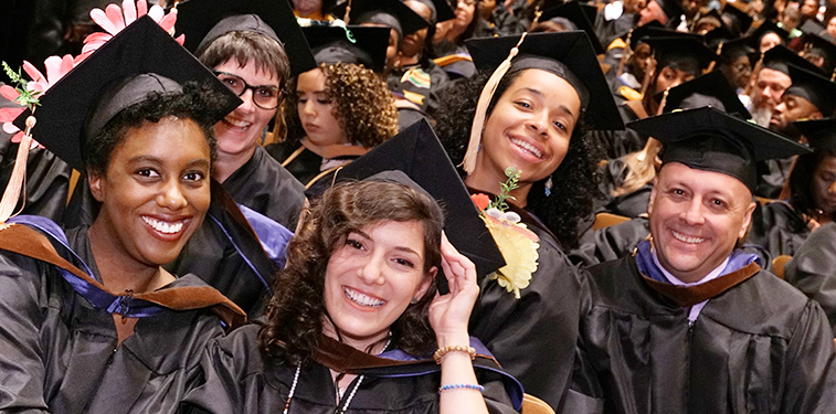 Students celebrate in cap and gowns at 2019 graduation ceremony.