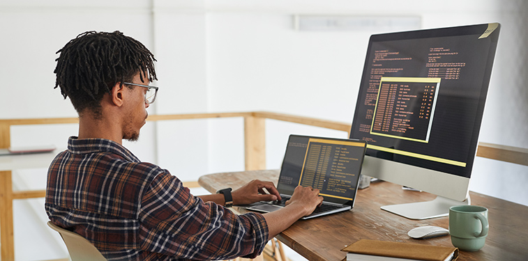 Male African American IT student coding on Mac laptop with monitor