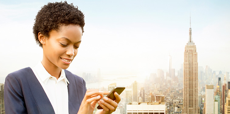 Young African American woman with short curly hair, dressed in business casual attire (blue sweater and white button down shirt) with a smart phone in her hand. The NYC cityscape is in the background.