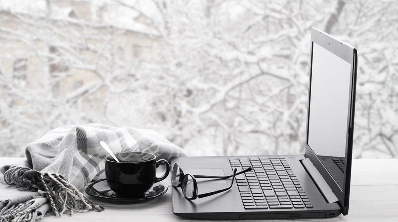 Laptop, coffee mug, and reading glasses with a winter backdrop