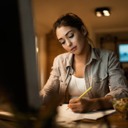 Hispanic young lady sitting at table studying notes