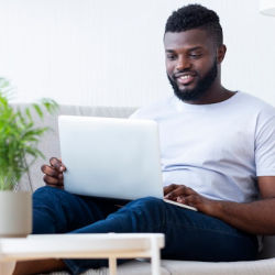 African American man sitting on the sofa studying on a laptop looking at the screen.