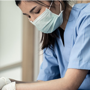 An Asian nursing wearing a mask sitting down taking a moment to herself
