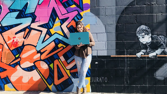 Yerelyn Nunez posed on her laptop in front a graffiti mural