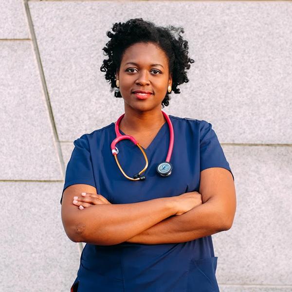 Phara Souffrant, arms crossed, wearing nurse scrubs