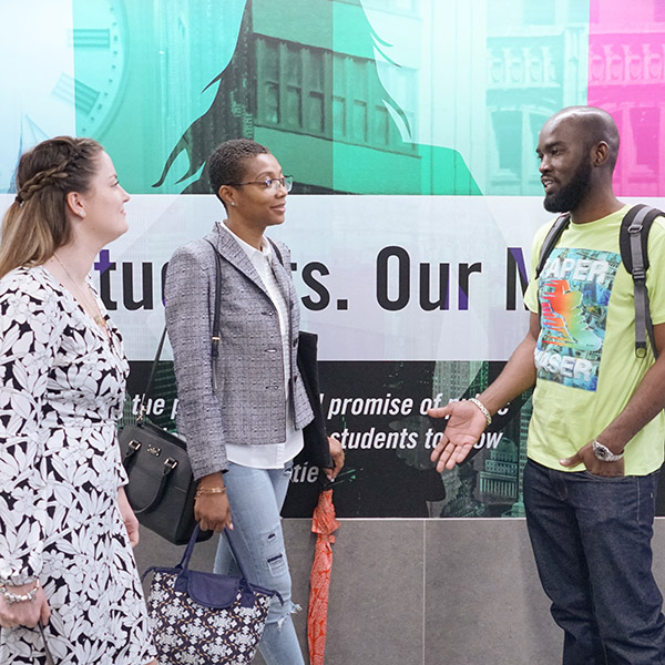 Three CUNY SPS students standing in campus lobby and talking