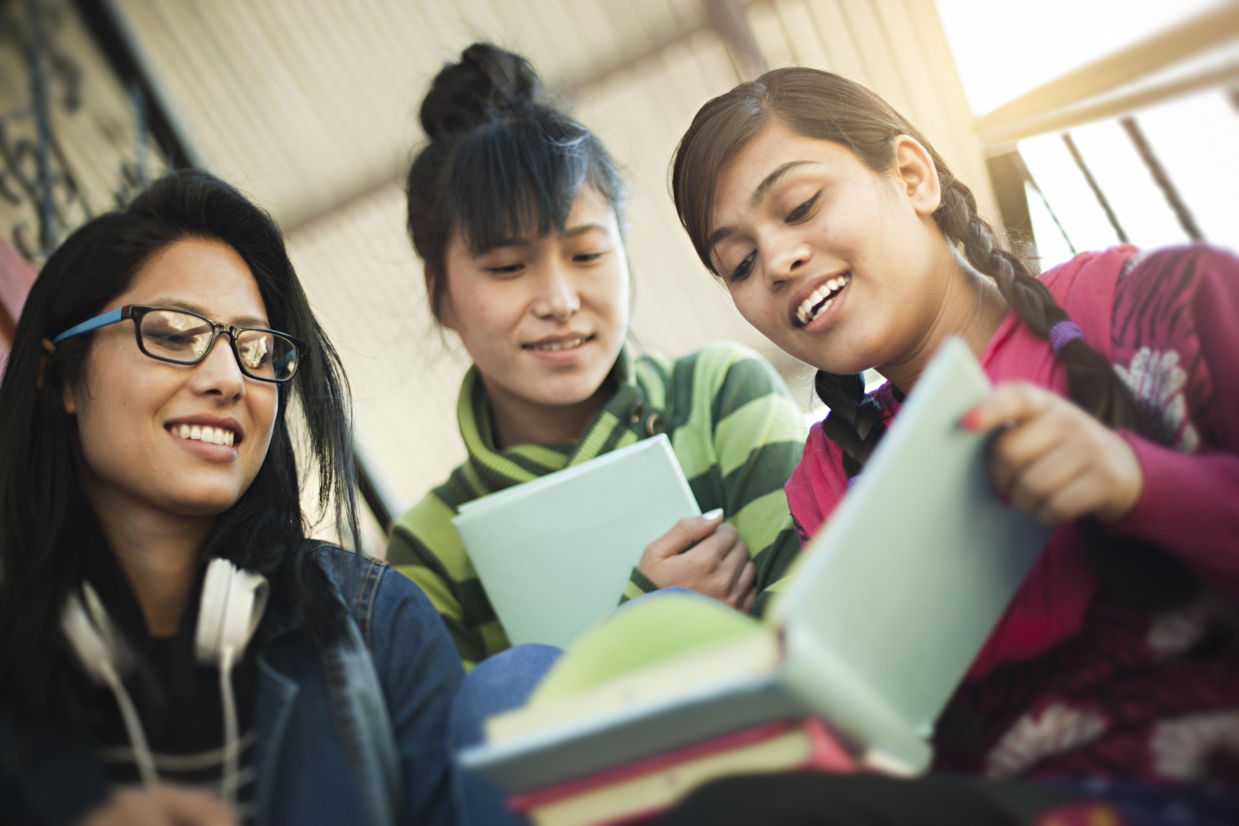 Three girls reading a book
