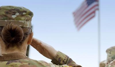 Military woman saluting the American flag
