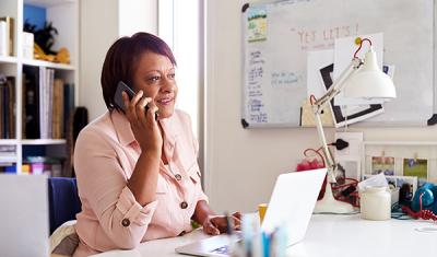 African American woman on the phone working at her desk.