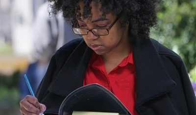 Woman writing in a notebook outside