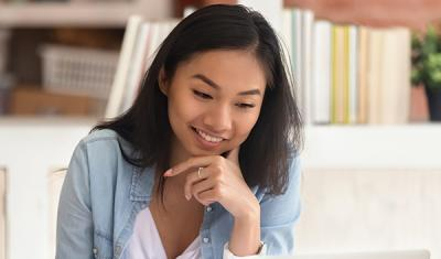 Smiling Asian undergraduate student studying in library with laptop