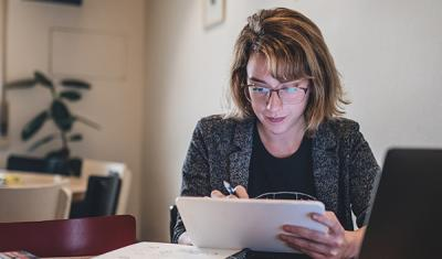 Woman in home office writing down notes in tablet