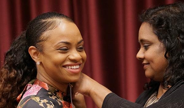 African American female nursing student receiving her pin during nursing convocation pinning ceremony