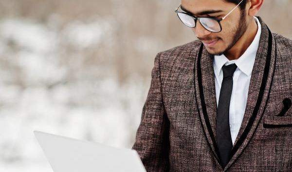 South Asian Male Student Wearing Blazer and Holding Laptop in Snowy Woods