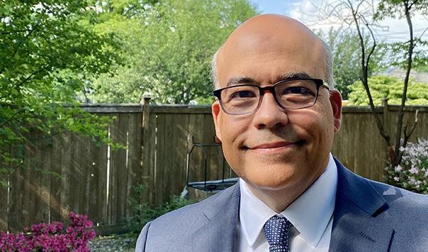 Interim Dean Jorge Silva-Puras smiling, wearing blue suit with glasses