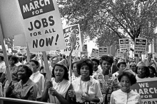 Photo of hundreds of African American women marching in protest with signs about jobs and integrating schools.