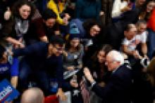 Group of young voters crowded around Presidential candidate Bernie Sanders