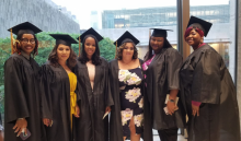 Group of graduates standing together in commencement regalia