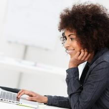 African American business woman typing on laptop