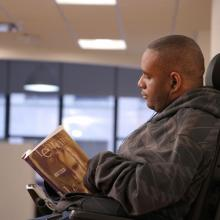 Disability studies student at CUNY SPS reading book in classroom