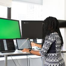 Female IT worker on laptop with two monitors
