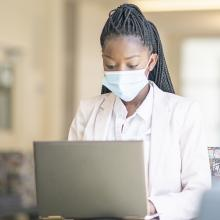 Female student typing on laptop while wearing mask