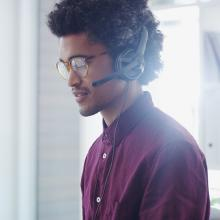 Shot of young man in IT profession using a headset in a modern office