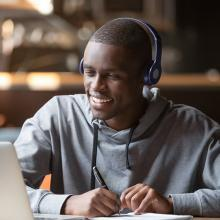 Smiling young male African student wearing headphones looking at laptop screen and writing notes in cafe