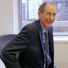 CUNY SPS founding dean John Mogulescu smiling in his office