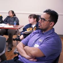 Male CUNY SPS student arms folded and seated during on campus event