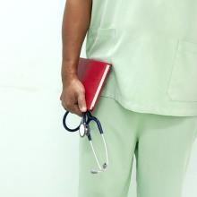 Male nurse in scrubs holding notebook