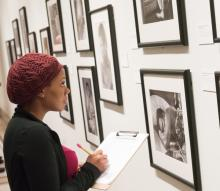 Woman standing in front of museum art writing notes in a notebook