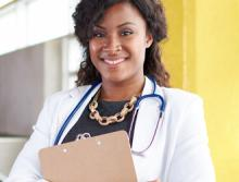 Nurse in white coat and stethoscope holding a clipboard smiling at the camera.