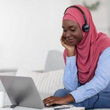 Smiling Black Muslim Woman Watching Webinar on Laptop
