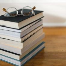 Stack of books and eyeglasses sitting on top