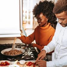 Young African American couple cooking dinner in kitchen